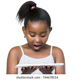 Close up portrait of cute little african girl with ponytail looking down at digital tablet.Kid with surprised facial expression Isolated on white background.