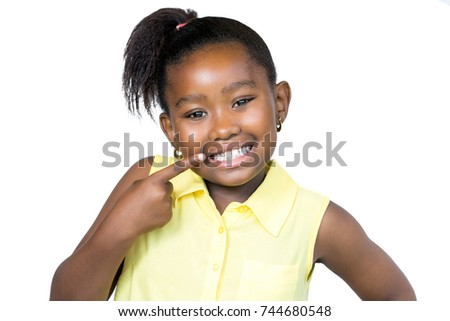 Close up  portrait of cute little african girl with ponytail pointing with finger at teeth.Isolated on white background.