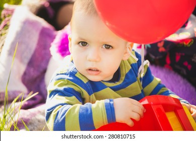 close up portrait of cute little baby boy playing with toys and balloons. small child looking at camera. face of beautiful kid among red air ballons. baby sitting on blanket at picnic.