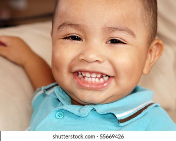 Close up portrait of cute little baby boy aged 2 with big toothy smile.