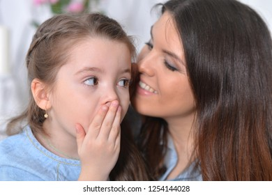 Close up portrait of cute little girl with mother hugging