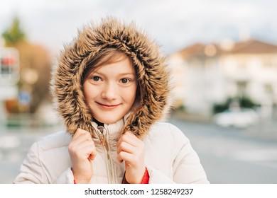 Close up portrait of cute little girl wearing winter jacket with fur hood