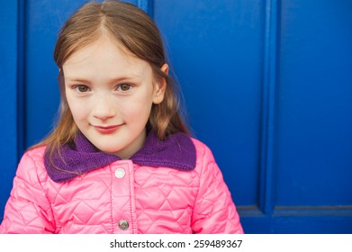 Close up portrait of a cute little girl of 7 years old, wearing bright pink jacket, sitting against blue wall