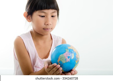 Close up Portrait of cute little girl holding earth sphere object. Isolated on white background.
