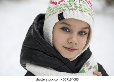 Close up portrait of a cute little girl in winter park