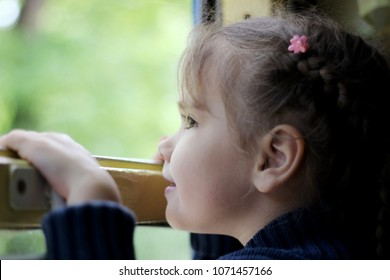 Close up portrait of cute little traveler girl looking through the window in the train, summer holidays, vacation and traveling concept, outdoor