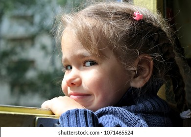 Close up portrait of cute little traveler girl looking through the open window in the train, summer holidays, vacation and traveling concept, outdoor