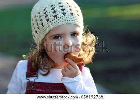 9bd55e53ec4 Close up portrait of cute one year old girl in a white knitted hat eating  cookie