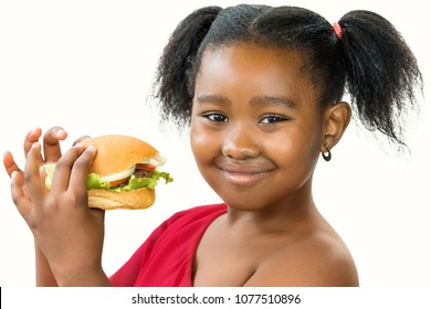 Close up portrait of cute ponytailed african girl holding appetizing hamburger.Kid smiling at camera isolated on white background.