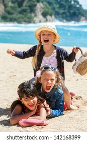 Close up portrait of cute threesome making human pile on beach.