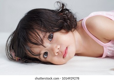 Close up portrait of a cute, wide-eyed asian little girl lying down in bed.