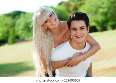 Close up portrait of cute young couple piggybacking outside.