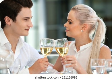 Close up portrait of cute young couple celebrating special moment with white wine.