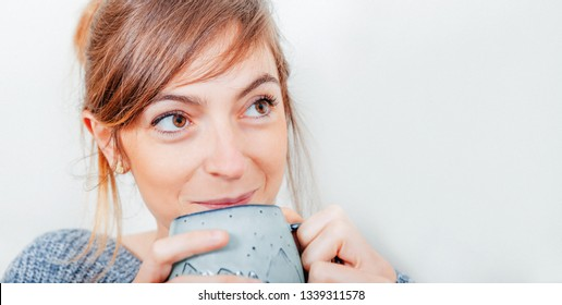 close up portrait of a cute young woman while holding a cup and smiling and looking up on white background with space for text