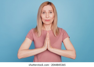 Close up portrait of cute young woman begging say please and show pleading gesture standing over blue background