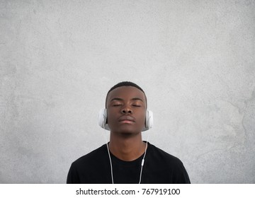 Close up portrait of dark skinned man with closed eyes, has headphones, listens to favourite music. Teenager enjoys audio track isolated on white gray wall