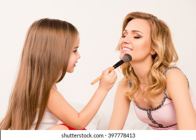 Close up portrait of daughter applying powder on her mom's face