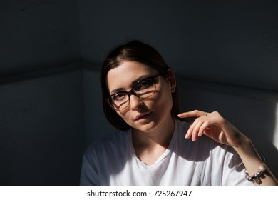 Close up portrait  with deep shadow of young pretty beautiful woman with glasses in white t-shirt sitting in a cafe