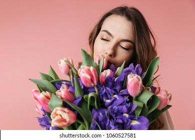 Close up portrait of a delighted young girl in dress holding big bouquet of irises and tulips isolated over pink background
