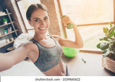 Close up portrait of delightful beautiful ideal slim sportive powerful muscular positive woman dressed in tight gray top demonstrating her biceps taking selfie having video call