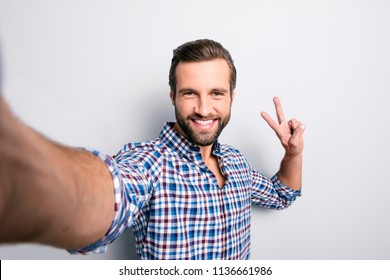 Close up portrait of delightful satisfied emotional cute handsome careless restless  with beaming toothy smile blogger dressed in blue checkered shirt isolated on gray background copy-space