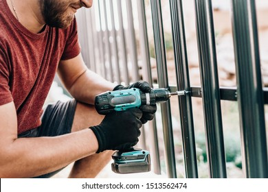 Close up portrait and details of caucasian male worker using screwdriver and screwing metal fence