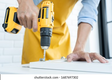 Close up portrait and details of caucasian male worker using electric screwdriver instrument in hand and repairing new wooden desk, home improvement concept