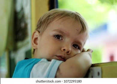 Close up portrait of dreamily 3 years old boy looking at camera during his first train travel, summer holidays, vacation and traveling concept, outdoor