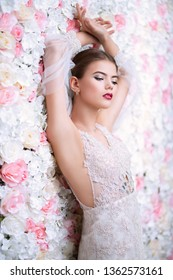 A close up portrait of a dreamy lady in a wedding dress posing indoor over the flowers. Wedding, beauty, fashion.