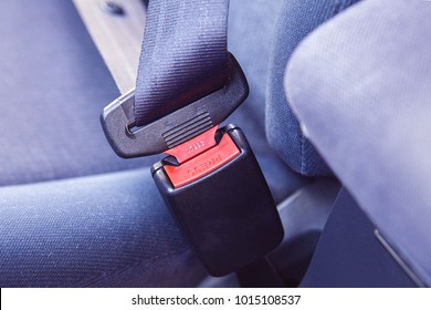 Close up portrait of a driver hand fastening seatbelt in a car