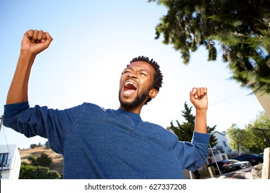 Close up portrait of ecstatic handsome man celebrating with arms outstretched