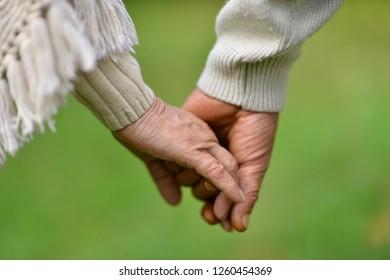 Close up portrait of elderly couple holding hands