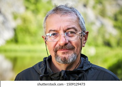 Close up portrait of an elderly intelligent man in glasses and with a gray beard. Smiling face of an educated man of retirement age. Outdoor portrait of an old man with a blurry green background.