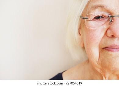 Close up portrait of an elderly woman in eyeglasses. Half face elderly woman. Eye diseases concept.