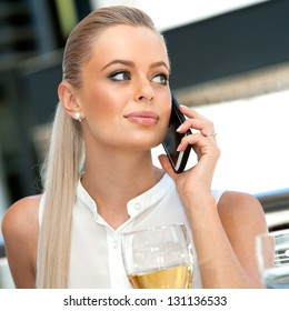 Close up portrait of elegant businesswoman talking on smart phone during lunch.