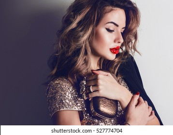 Close up portrait of elegant luxurious woman in trendy gold sequin party dress . Elegant wavy hairstyle, bright make up, red lips.