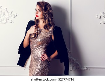 Close up portrait of elegant luxurious woman in trendy gold sequin party dress . Elegant wavy hairstyle, bright make up, red lips. Holding trendy evening purse.