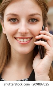 Close up portrait of an elegant professional business woman standing in a classic city, smiling and having a phone call conversation with her smartphone device. Business technology outdoors.