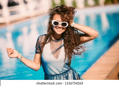 Close up portrait of elegant stunning woman, tanned perfect skin, full sexy right lips, stylish mirrored sunglasses, relaxed near pool, lay and getting sunbathe, bright sunny colors, summer style.