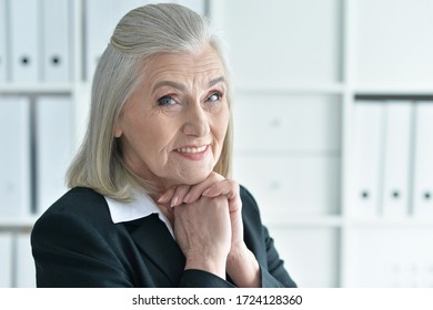 Close up portrait of emotional old businesswoman in office posing in front of camera