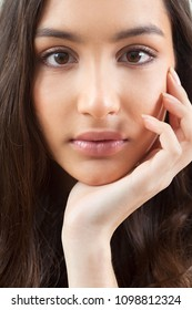 Close up portrait of ethnic asian young woman face looking with perfect skin care, leaning on hand. Indian features beautiful female, racial beauty, natural make up cosmetics, youth lifestyle.