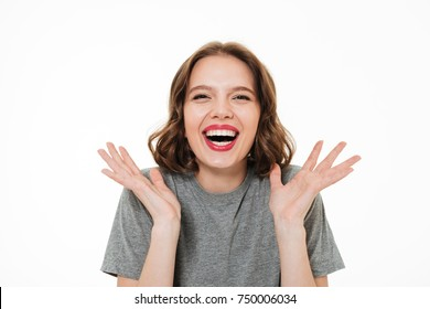 Close up portrait of an excited smiling woman with make-up laughing at camera and gesturing with hands isolated over white background