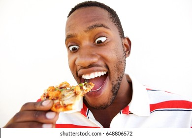 Close up portrait of excited young african man eating pizza