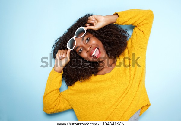 Close up portrait of excited young african female in sunglasses on blue background