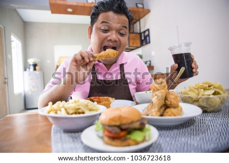 Close up portrait of excited young asian man eating in the dining room