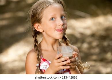 Close up portrait of expressive girl drinking chocolate milkshake.