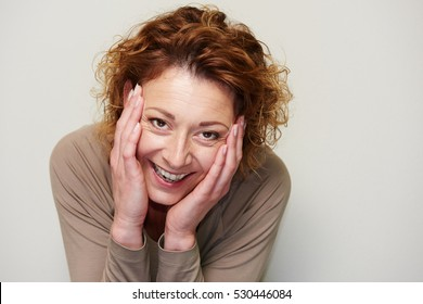 Close up portrait of expressive woman holding head in hands in surprise