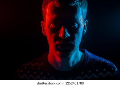 Close up portrait of the face of an adult serious man looking into the camera: straight nose, expressive eyes, ears, beard; illuminated with blue and red colored light on a black background.