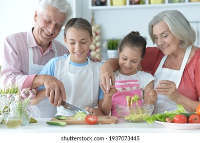 Close up portrait of family cooking together in kitchen