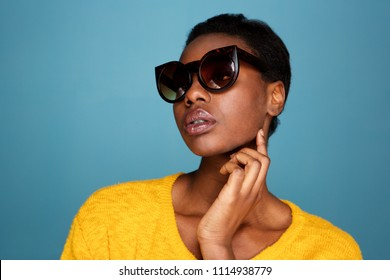 Close up portrait of fashionable black woman in sunglasses by blue wall